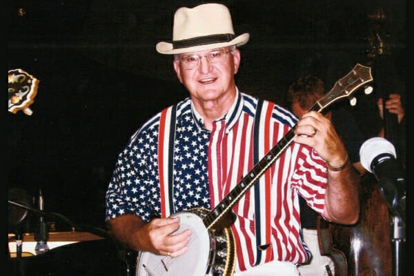 Dr. Buzby's father playing the banjo and wearing a stars and stripes shirt, photo