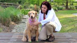 Integrative veterinarian Dr. Buzby kneeling beside dog that is wearing green ToeGrips® dog nail grips