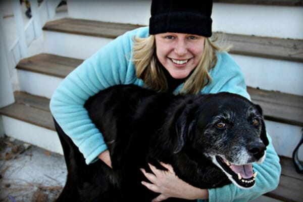 Black lab being hugged by owner while on the steps to the house, photo