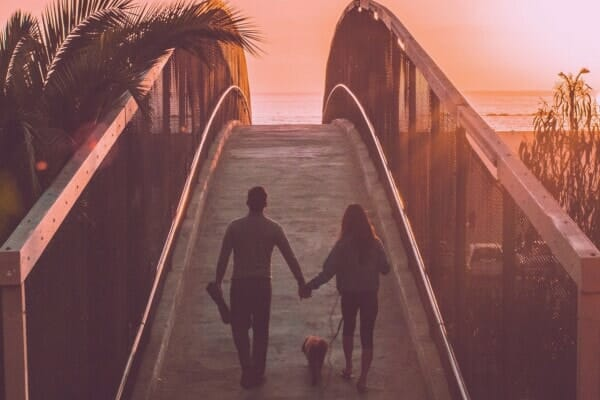 couple walking hand-in-hand over a beach boardwalk with dog, photo